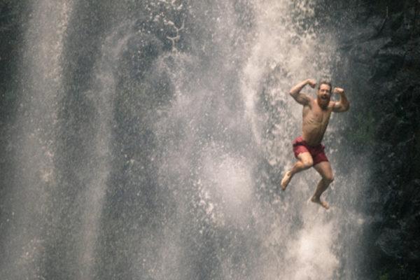 Man celebrating in waterfall